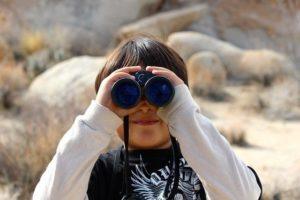 Kind schaut durch Fernglas