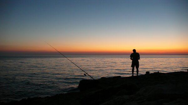 Sonnenuntergang Angler am Meer